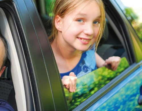 Young girl in car with dad during a road trip